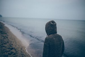 Person from the back in a hooded sweatshirt walking on a beach alone